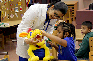 A girl plays with a yellow stuffed animal held by a member of the Brumback Dental staff.